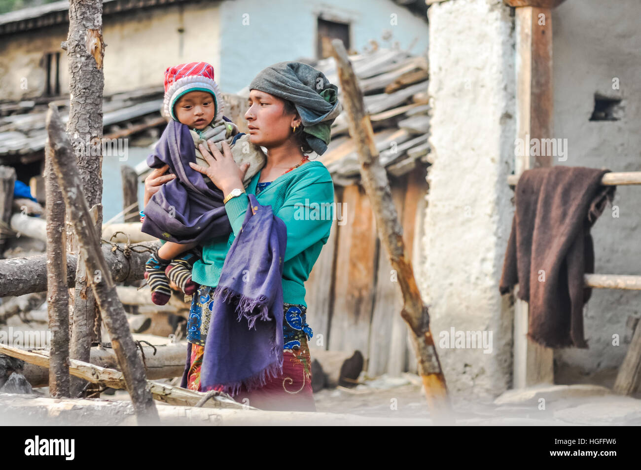 Dolpo, Nepal - circa May 2012: Native woman with grey headcloth wears green sweatshirt and holds her child covered - Stock Image