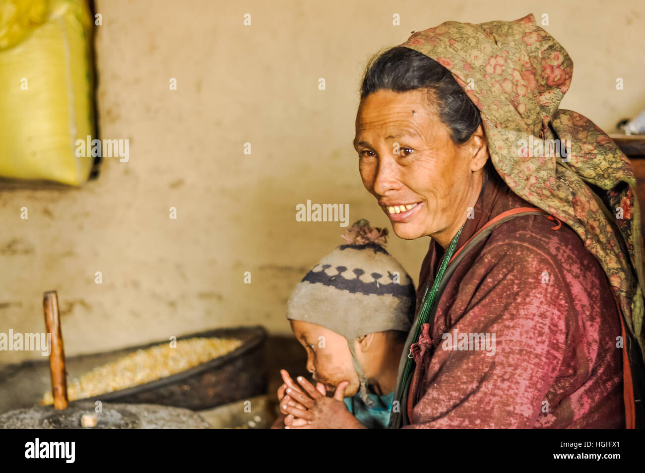 Dolpo, Nepal - circa May 2012: Native black-haired woman with large headcloth in purple clothes holds child and - Stock Image