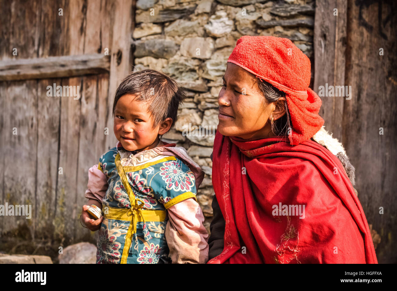 Beni, Nepal - circa May 2012: Mother in red scarf and headcloth kneels near her small daughter with brown hair and - Stock Image