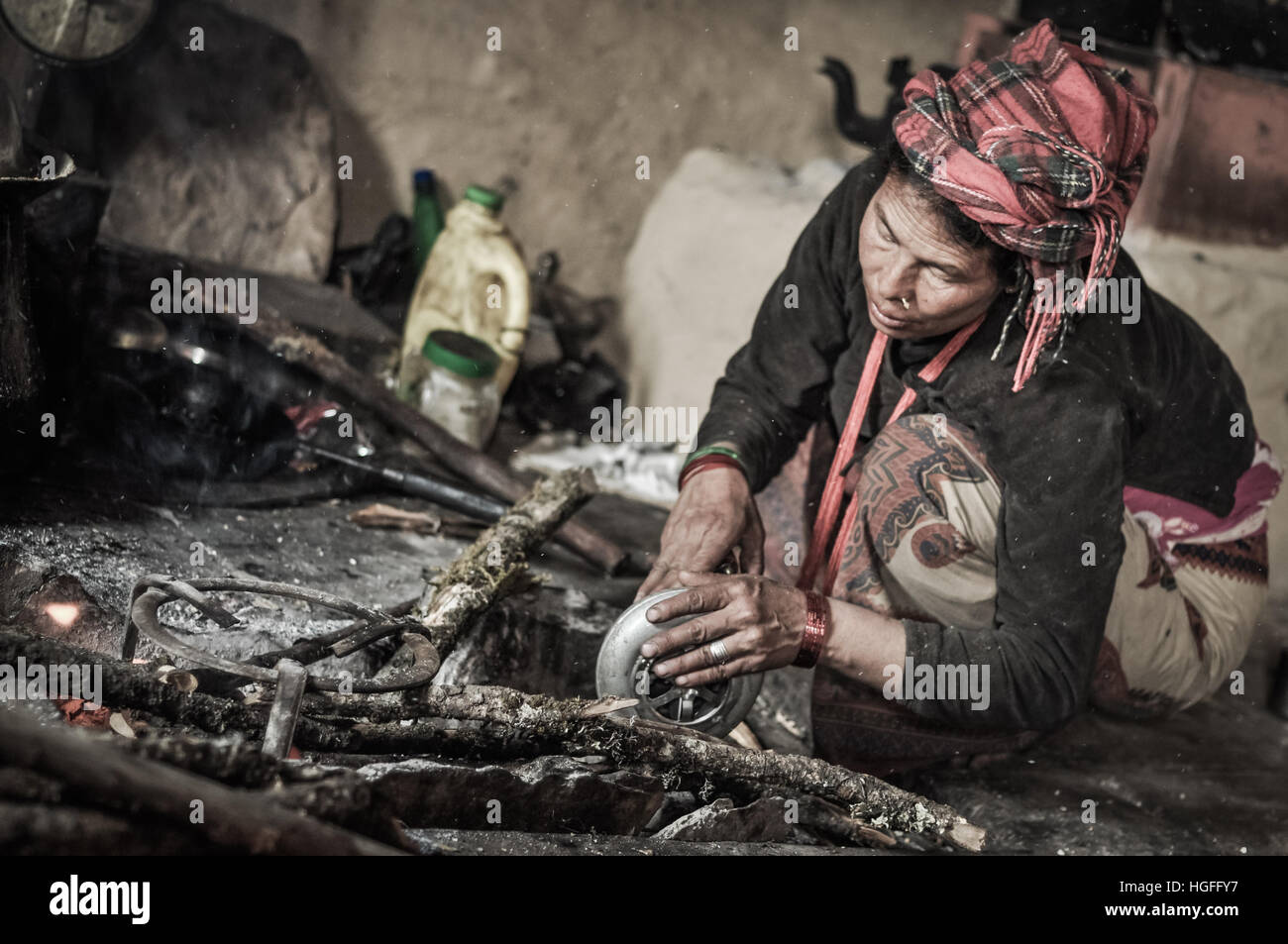 Dolpo, Nepal - circa May 2012: Native woman with red headcloth kneels next to wooden branches and works during preparation - Stock Image