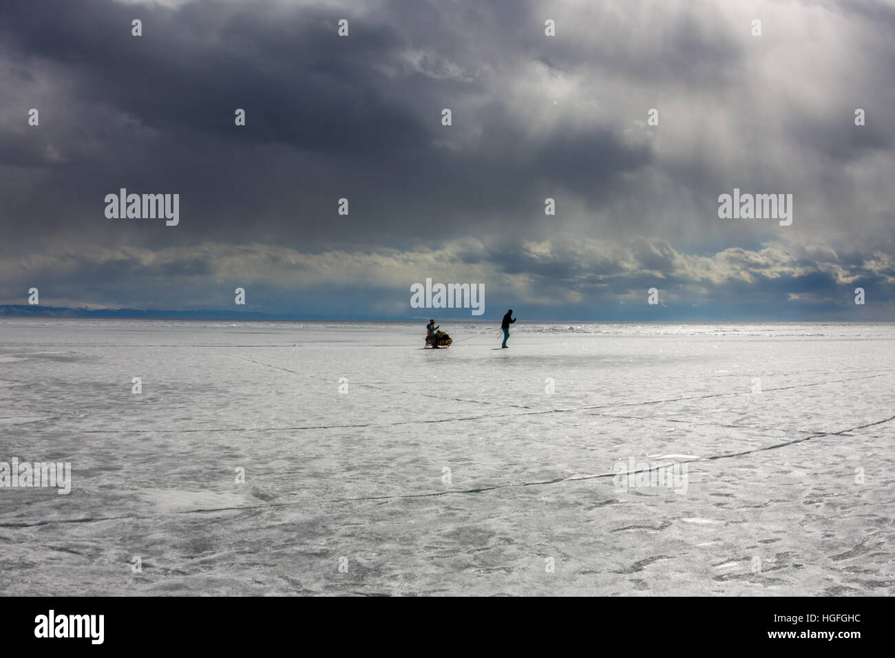 woman and a man with a sledge and trekking pole is ice of Baikal - Stock Image