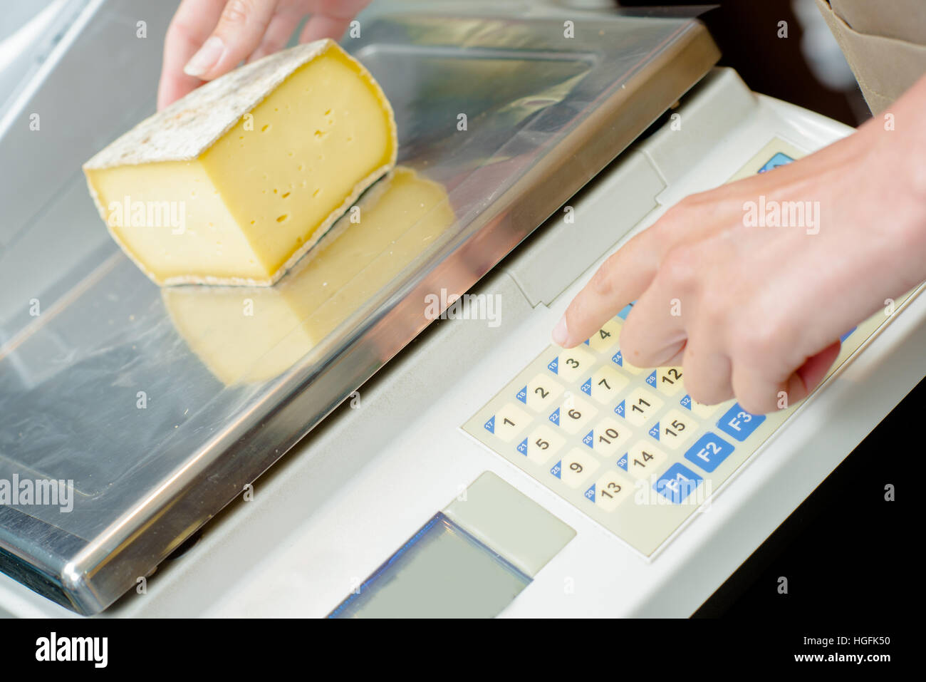 Weighing cheese on electronic scales - Stock Image