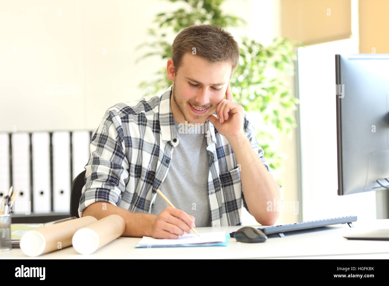Designer or architect working writing notes at office - Stock Image