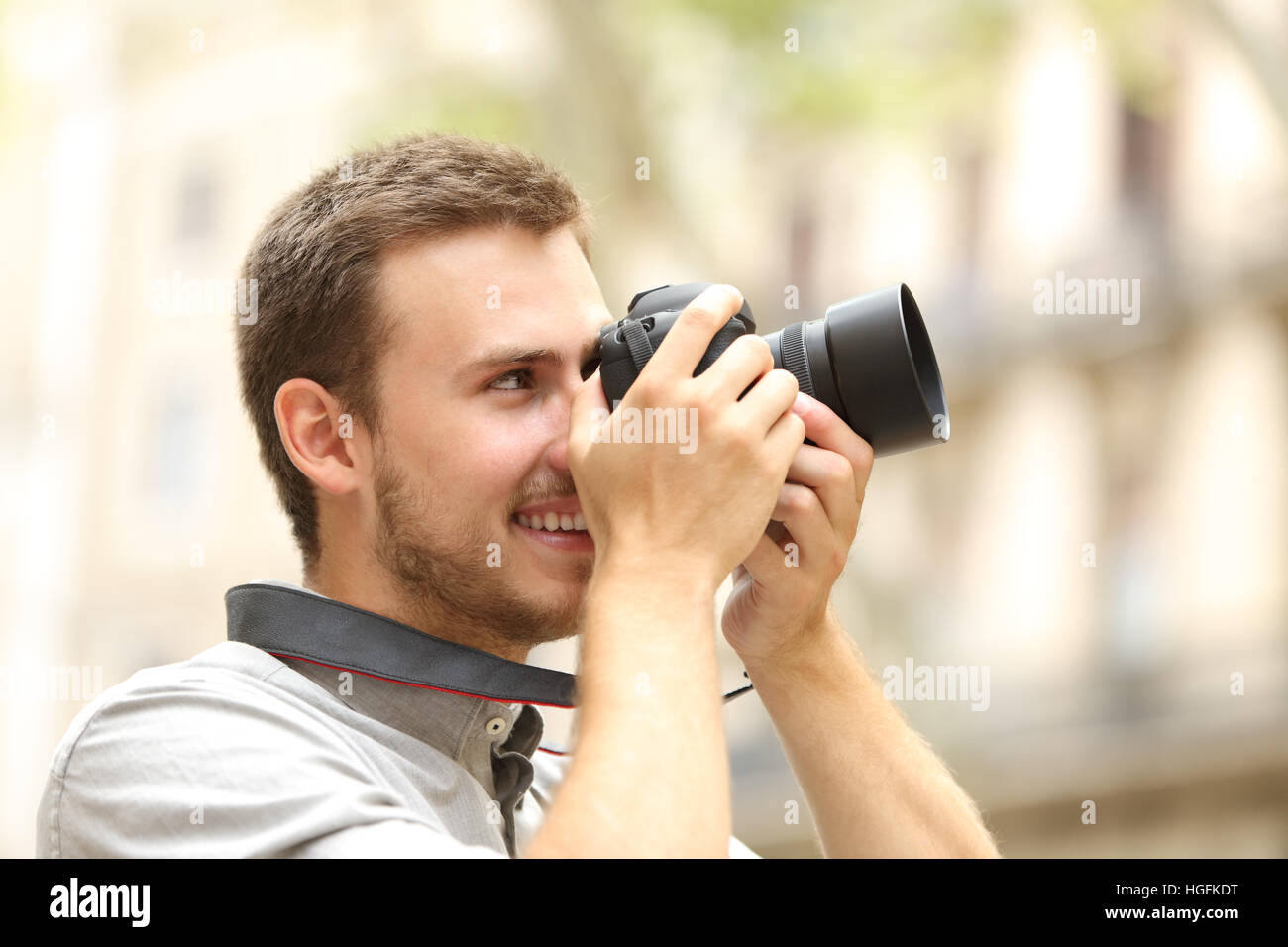 Side view of a happy man photographing with a dslr camera in the street of a city or town - Stock Image