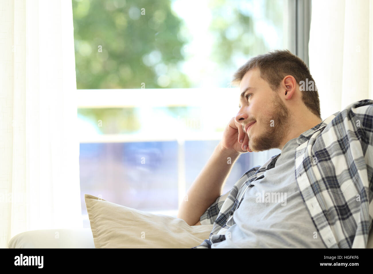 Portrait of a pensive man relaxing sitting on a couch and looking outdoors through a window in the living room at - Stock Image