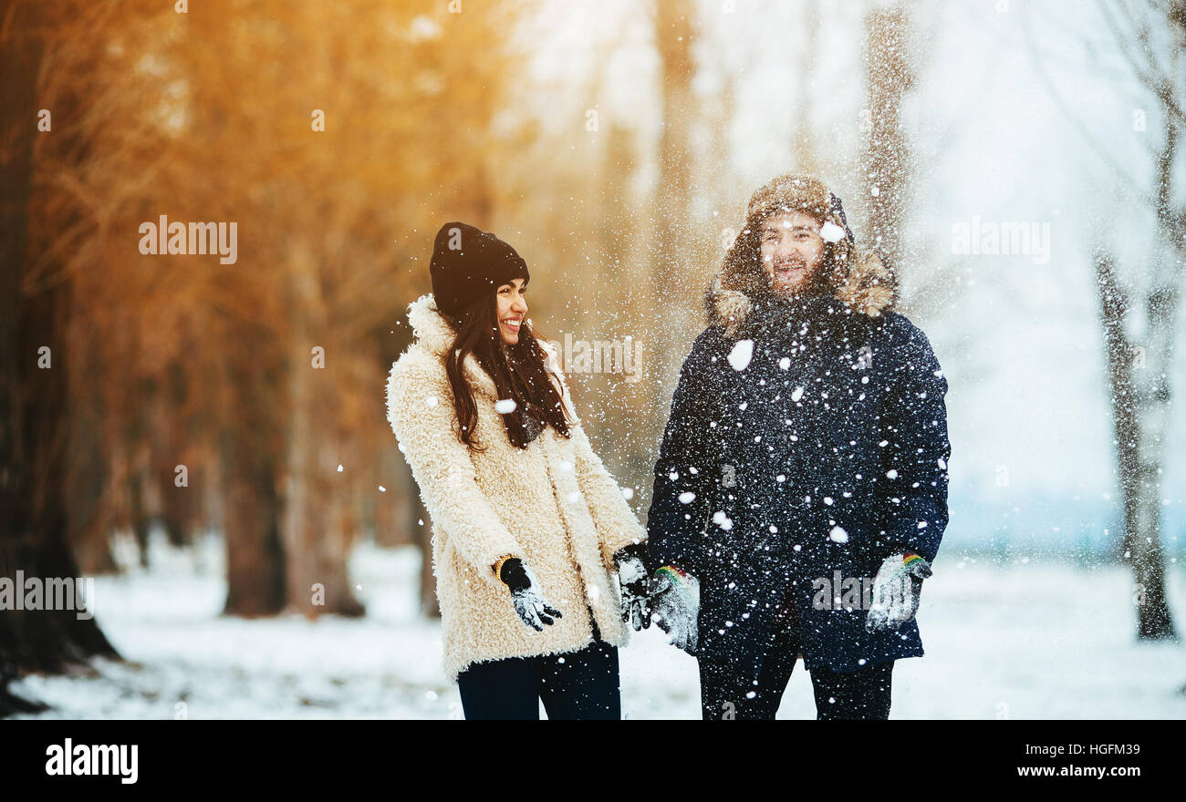 boy and girl playing with snow - Stock Image