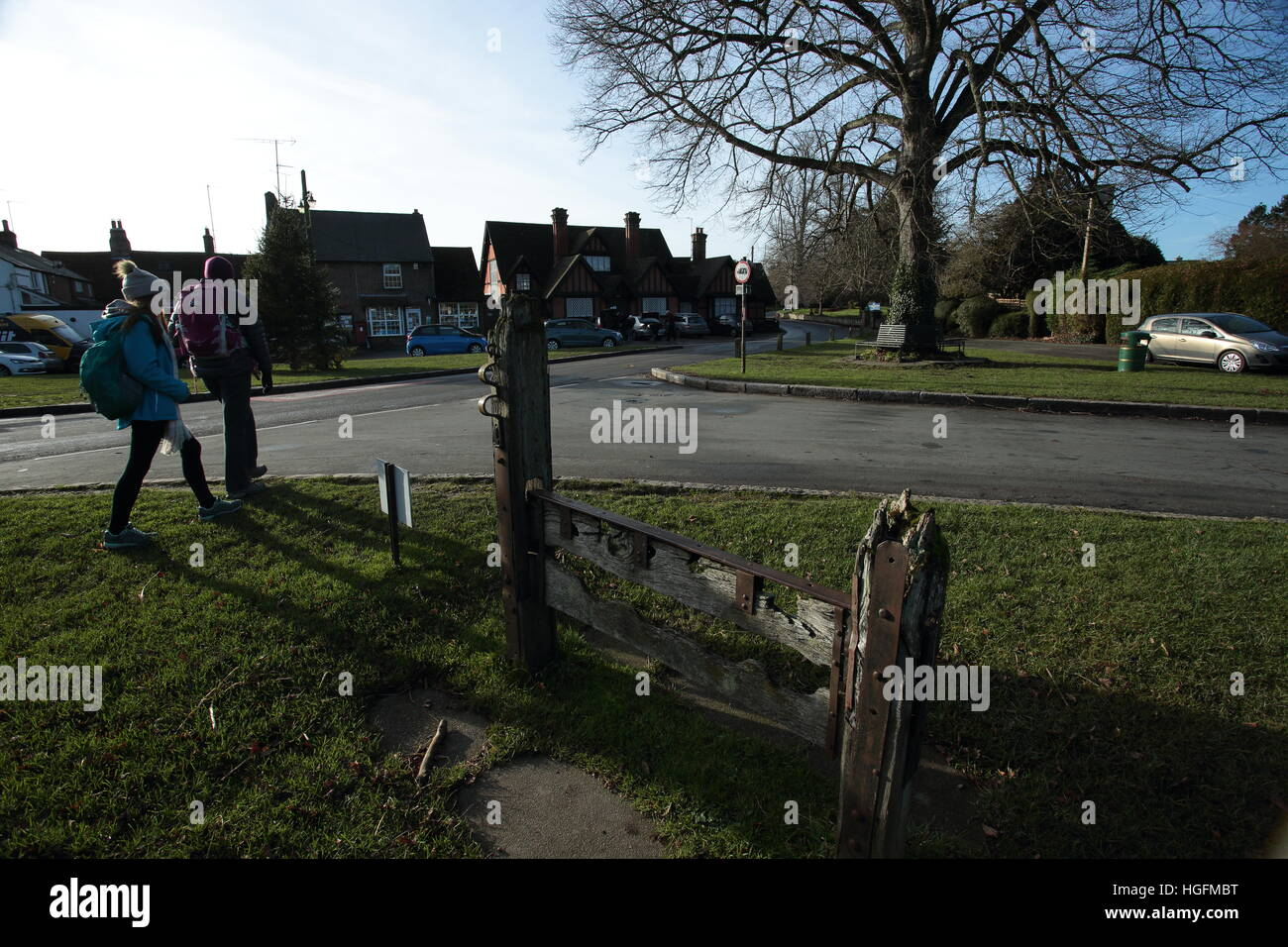 Two walkers by the stocks in Aldbury,Hertfordshire. - Stock Image