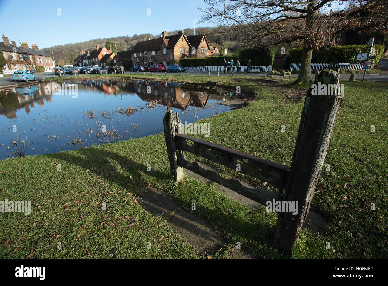 The pond in Aldbury,Hertfordshire on a sunny winters day,with the stocks in foreground. - Stock Image