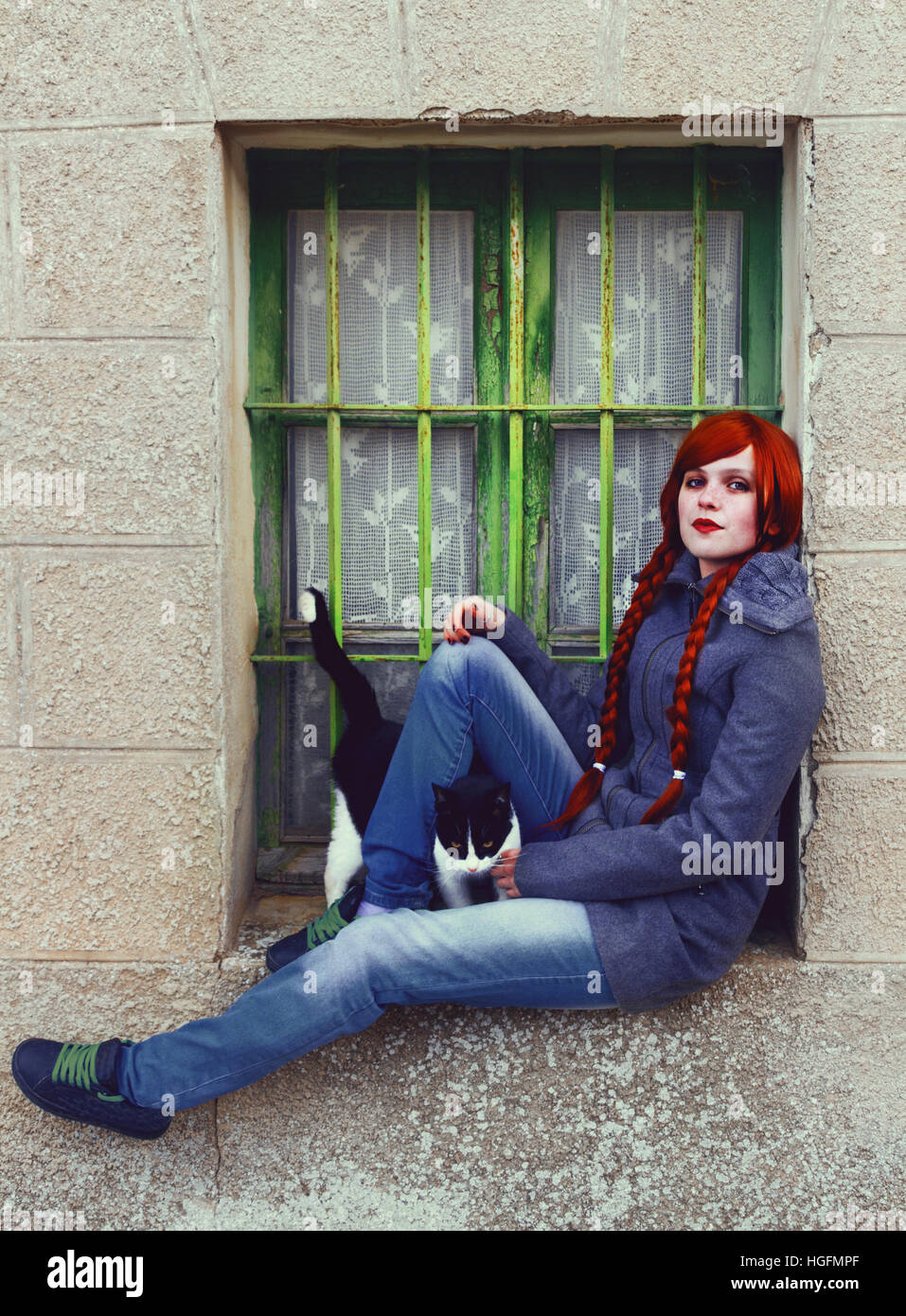 Young redhead woman, with two long braids, sitting near a old window - Stock Image