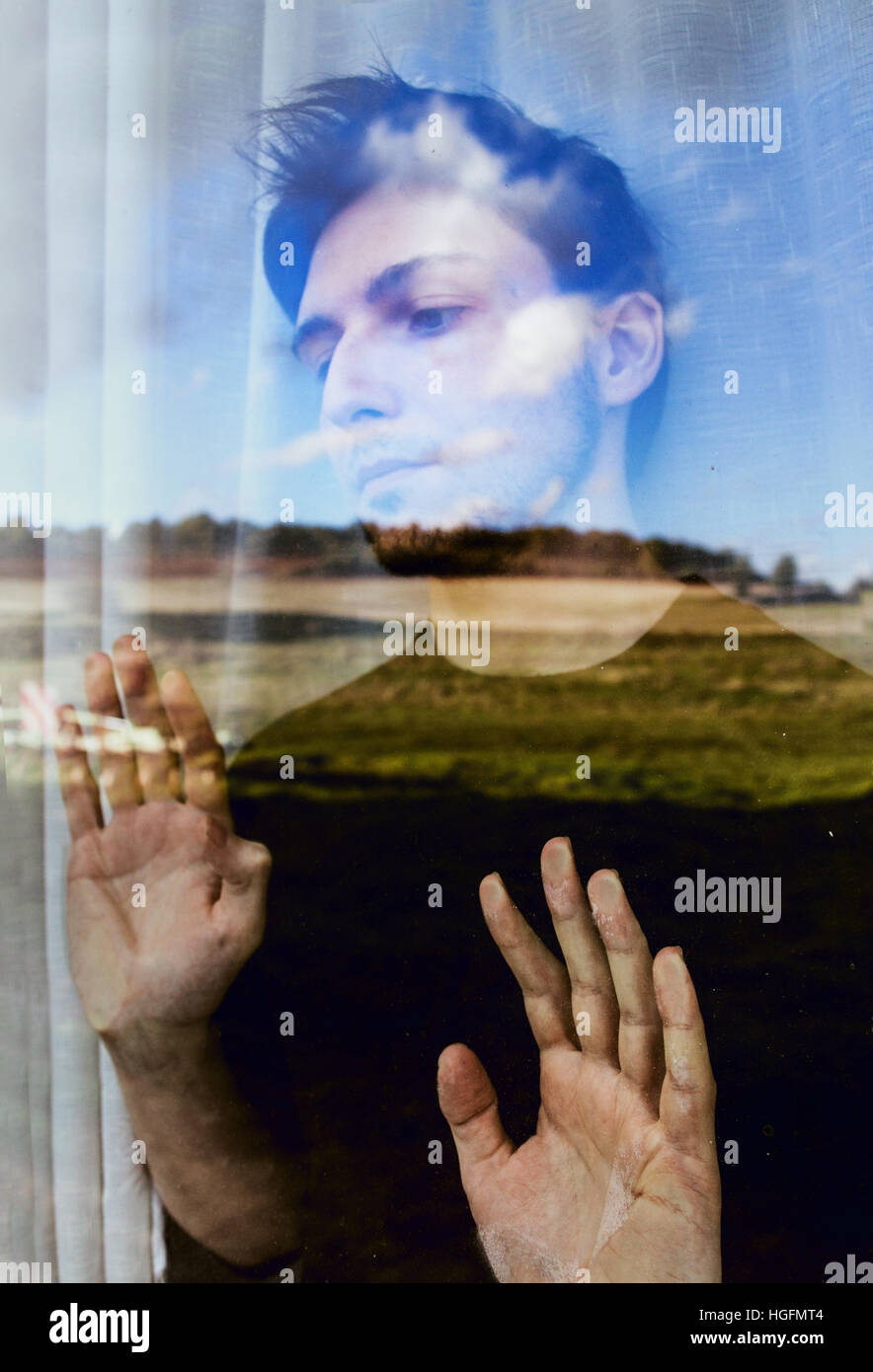 Young man dreaming with freedom looking through a window - Stock Image