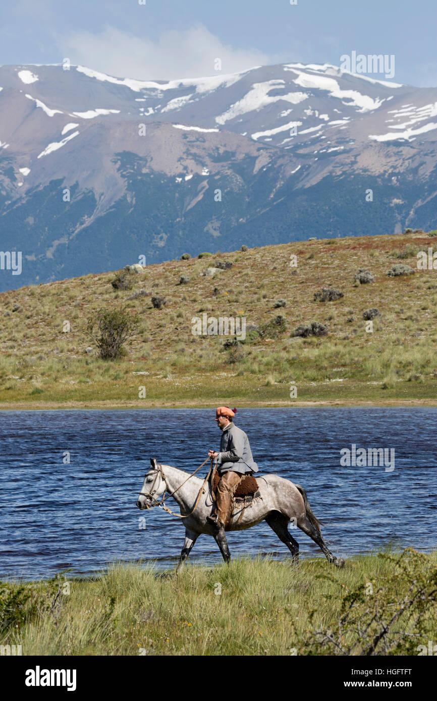 Gaucho on horse by lake at Estancia Alta Vista, El Calafate, Parque Nacional Los Glaciares, Patagonia, Argentina, South America Stock Photo