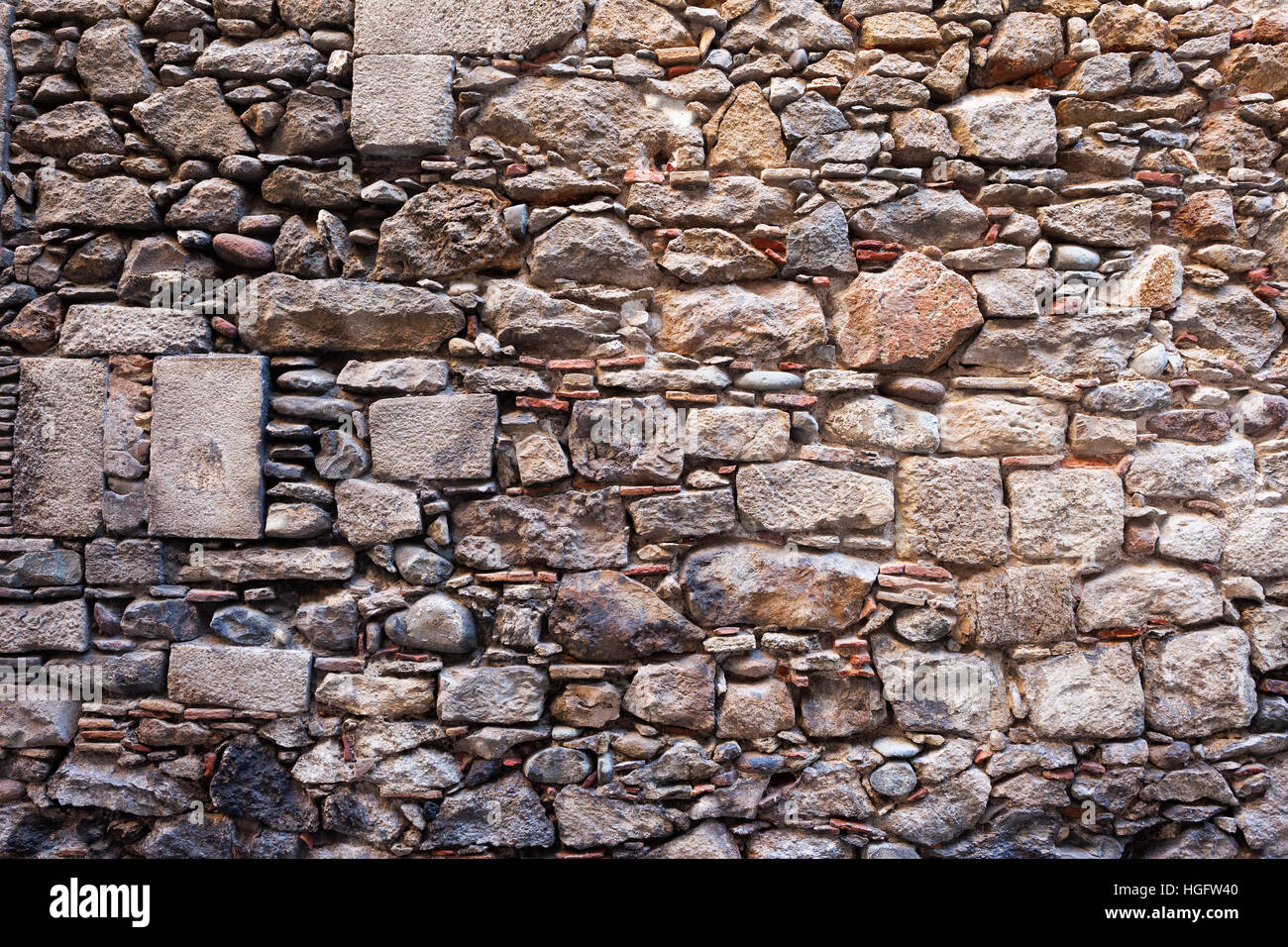 Medieval stone wall background or texture made with different sizes of rough cut stones and some bricks between, - Stock Image