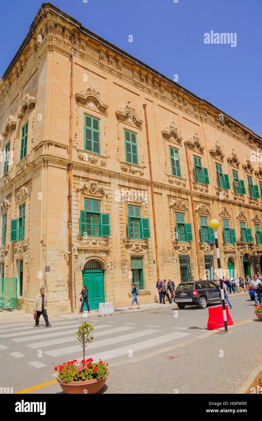 VALLETTA, MALTA - APRIL 13, 2012: Street scene with local businesses, locals and visitors, in Valletta, Malta - Stock Image