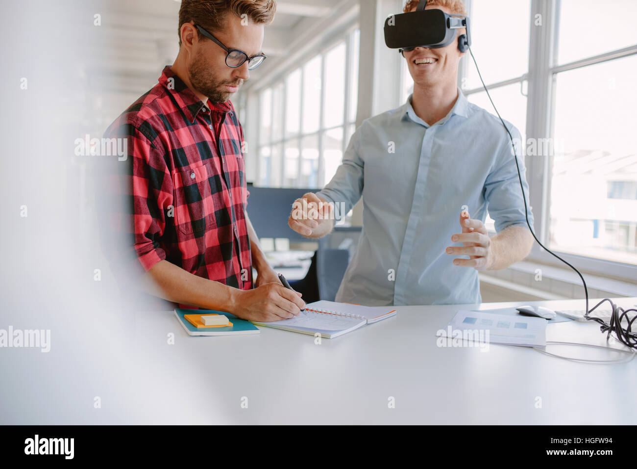 Young man writing notes with colleague wearing virtual reality goggles in office. Developers working on augmented - Stock Image