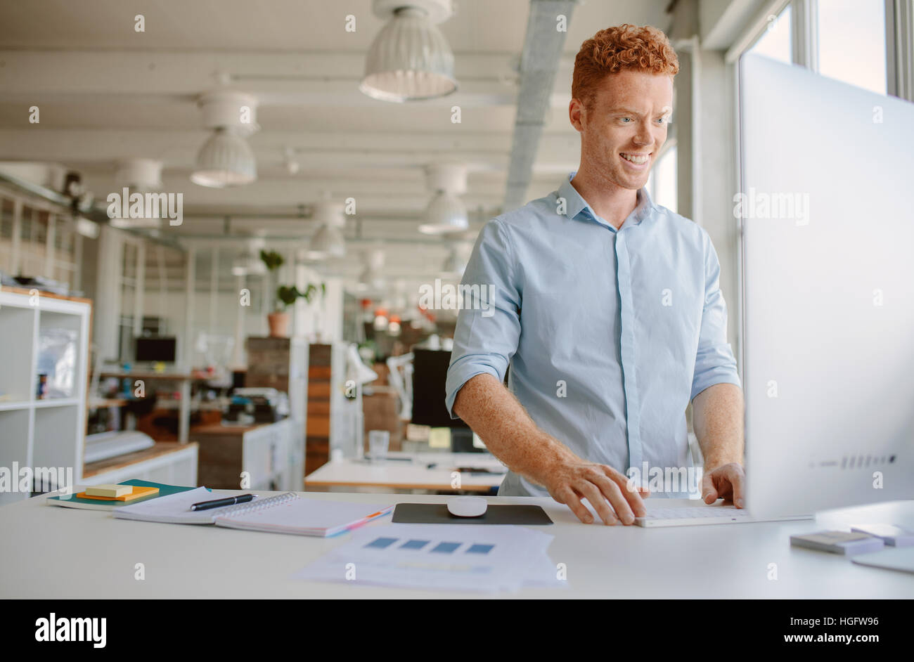 Shot of happy young man standing at his desk and working on computer. Businessman working in modern office. - Stock Image