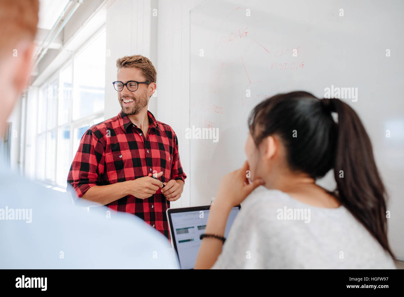 Happy young businessman in casuals giving presentation on white board to colleagues in conference room. Businessman - Stock Image