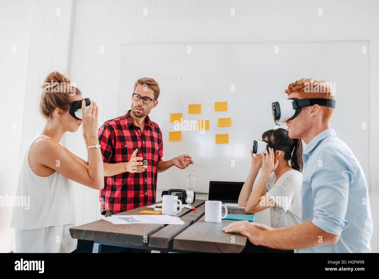 Young men and women sitting at a table with virtual reality goggles. Business team testing virtual reality headset - Stock Image