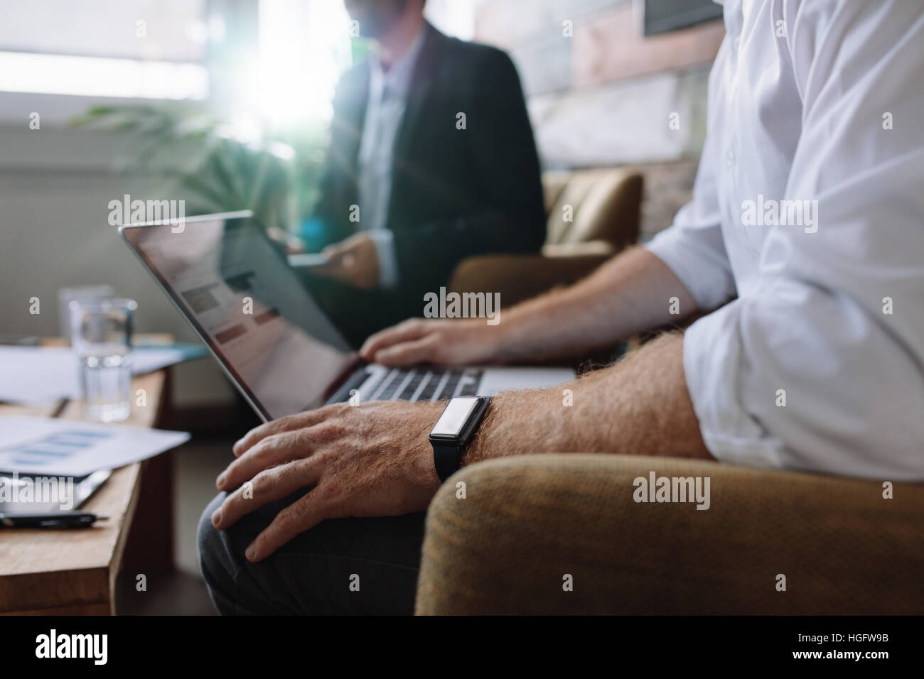 Businessman working on laptop during corporate meeting. Business people having a meeting in office. - Stock Image