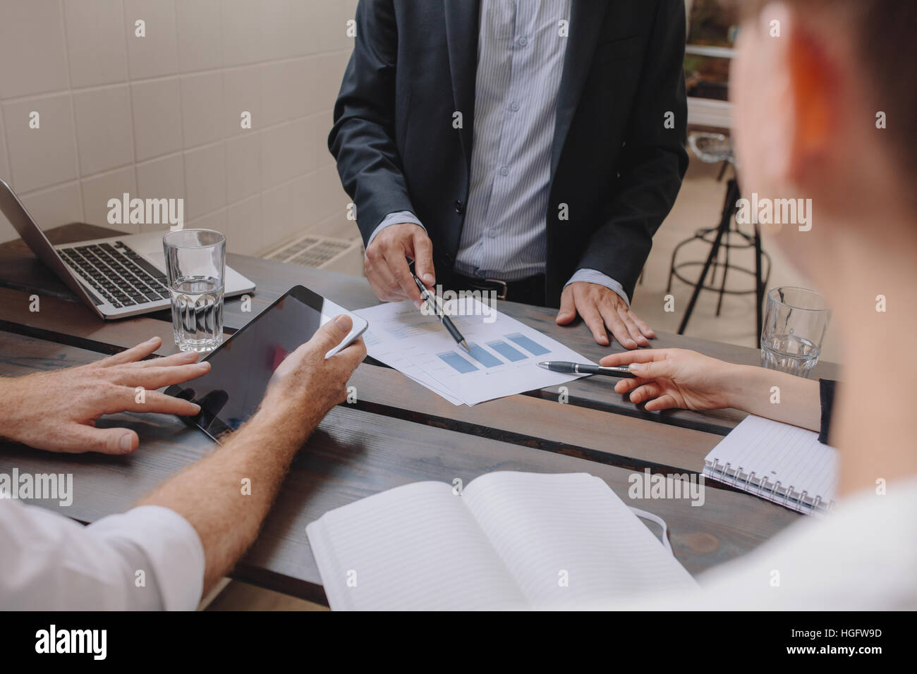 Close up shot of team of professionals meeting with digital tablet and charts. Business people discussing financial - Stock Image