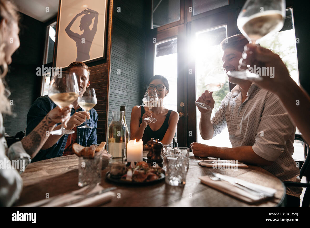 Diverse group of young people having wine at restaurant. Men and women meeting at a restaurant for dinner. - Stock Image