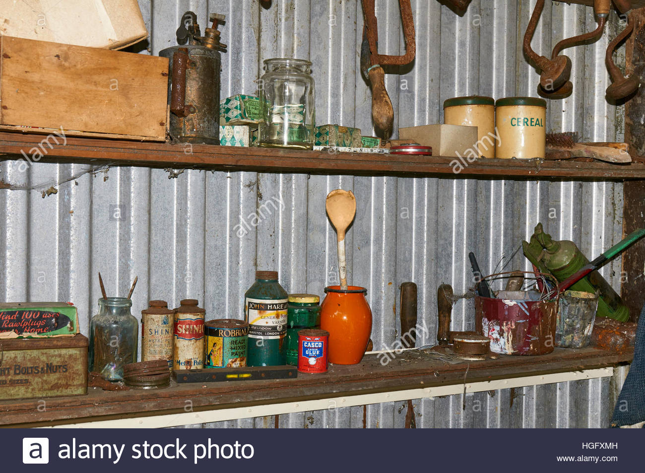 Inside a metal shed with tins glass jars and rusty tools on wooden ...