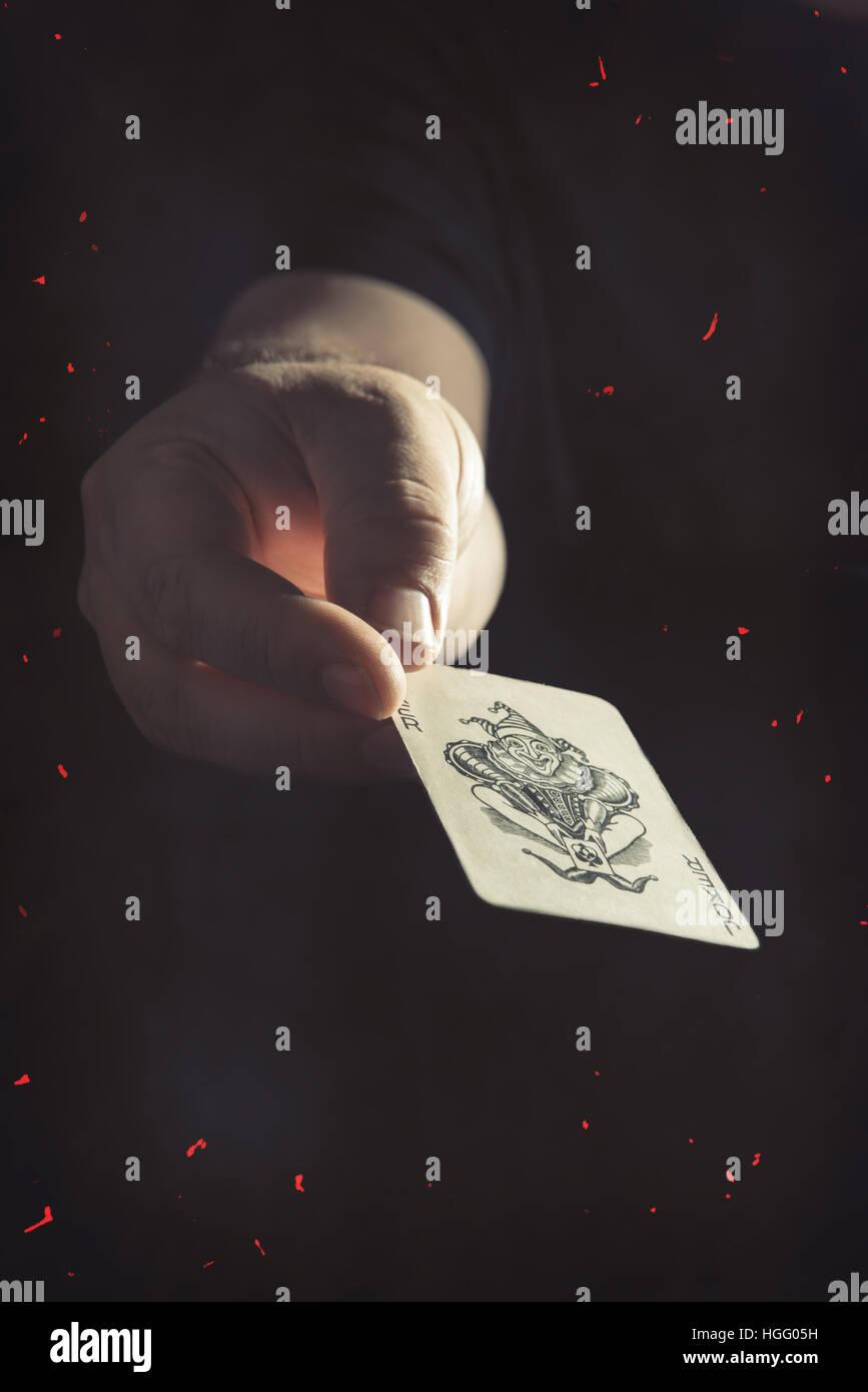 Male hand holding the Joker playing card - Stock Image