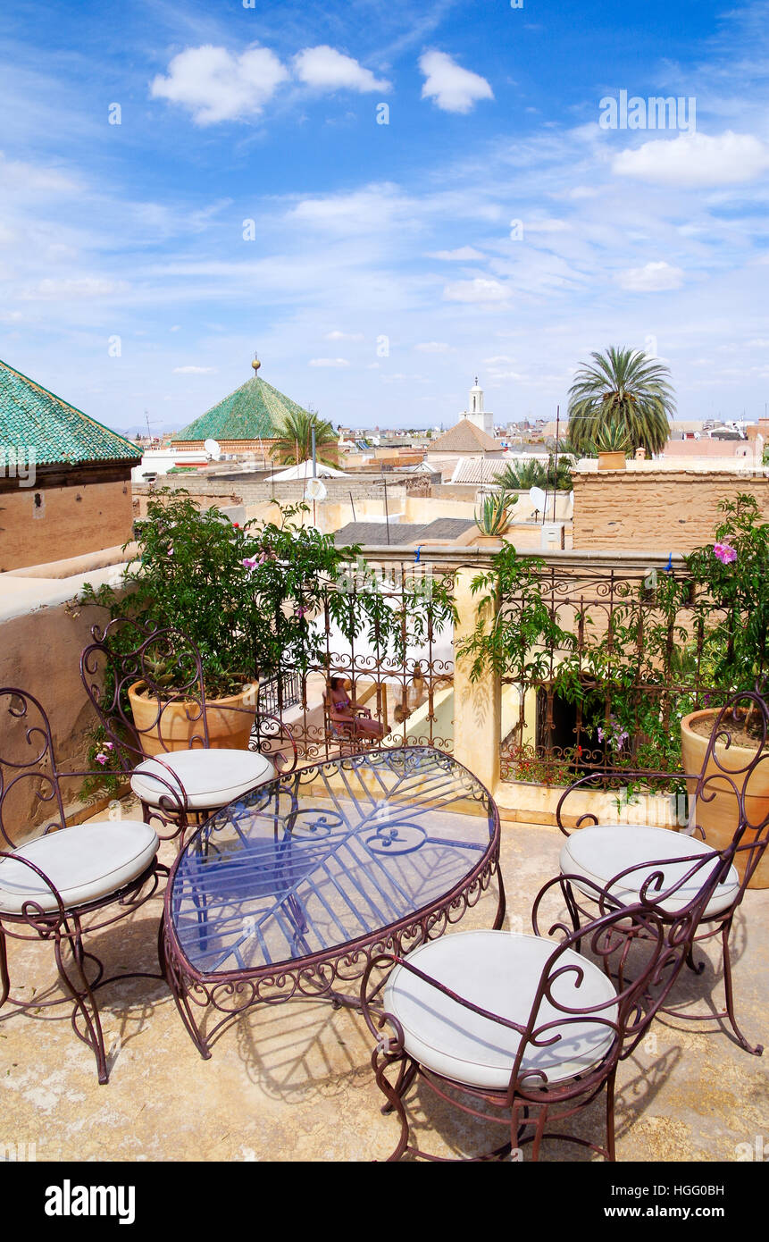 Rustic rooftop terrace with table and chairs in a Marrakech riyadh, Morocco - Stock Image