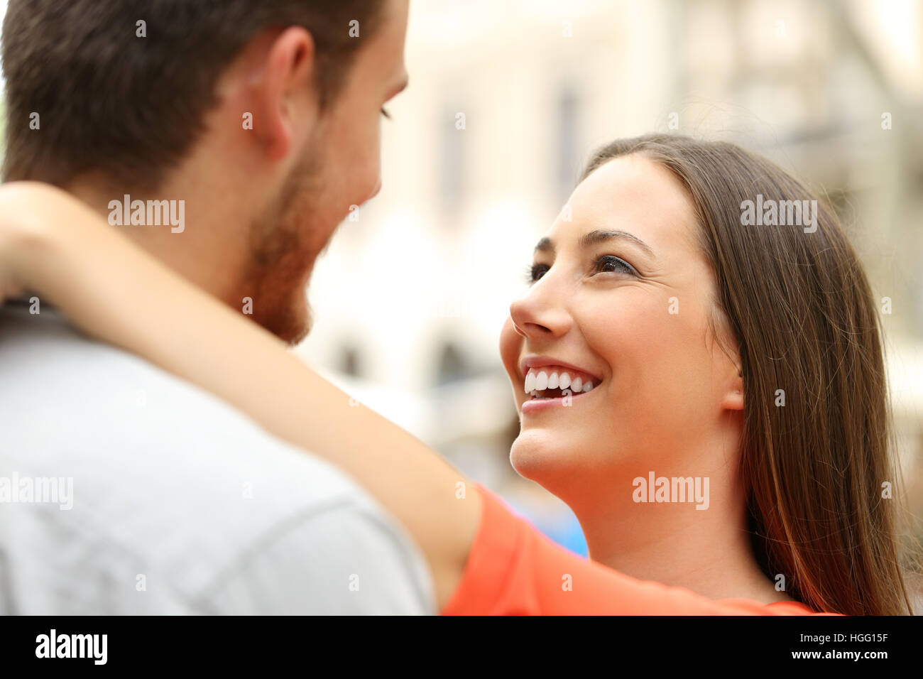 Happy couple in the street looking each other falling in love - Stock Image