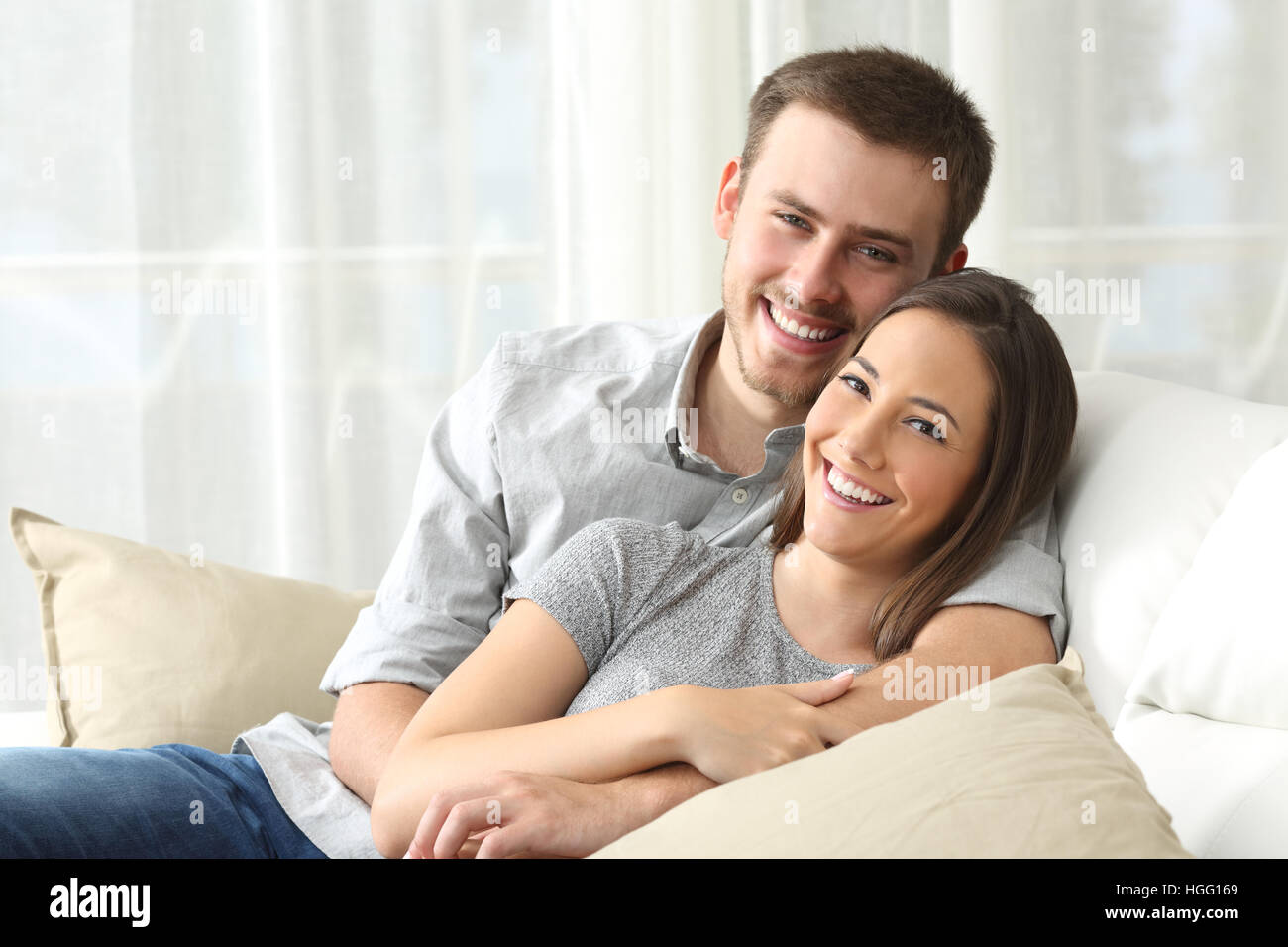 Happy couple sitting in a comfortable couch in the living room and looking at you at home Stock Photo