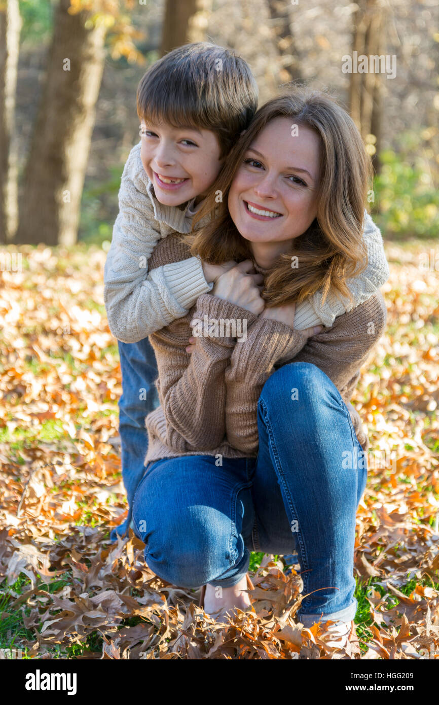 Mother and autistic son in the park. Child needs occupational, speech and motor skills therapy. IEP - Stock Image