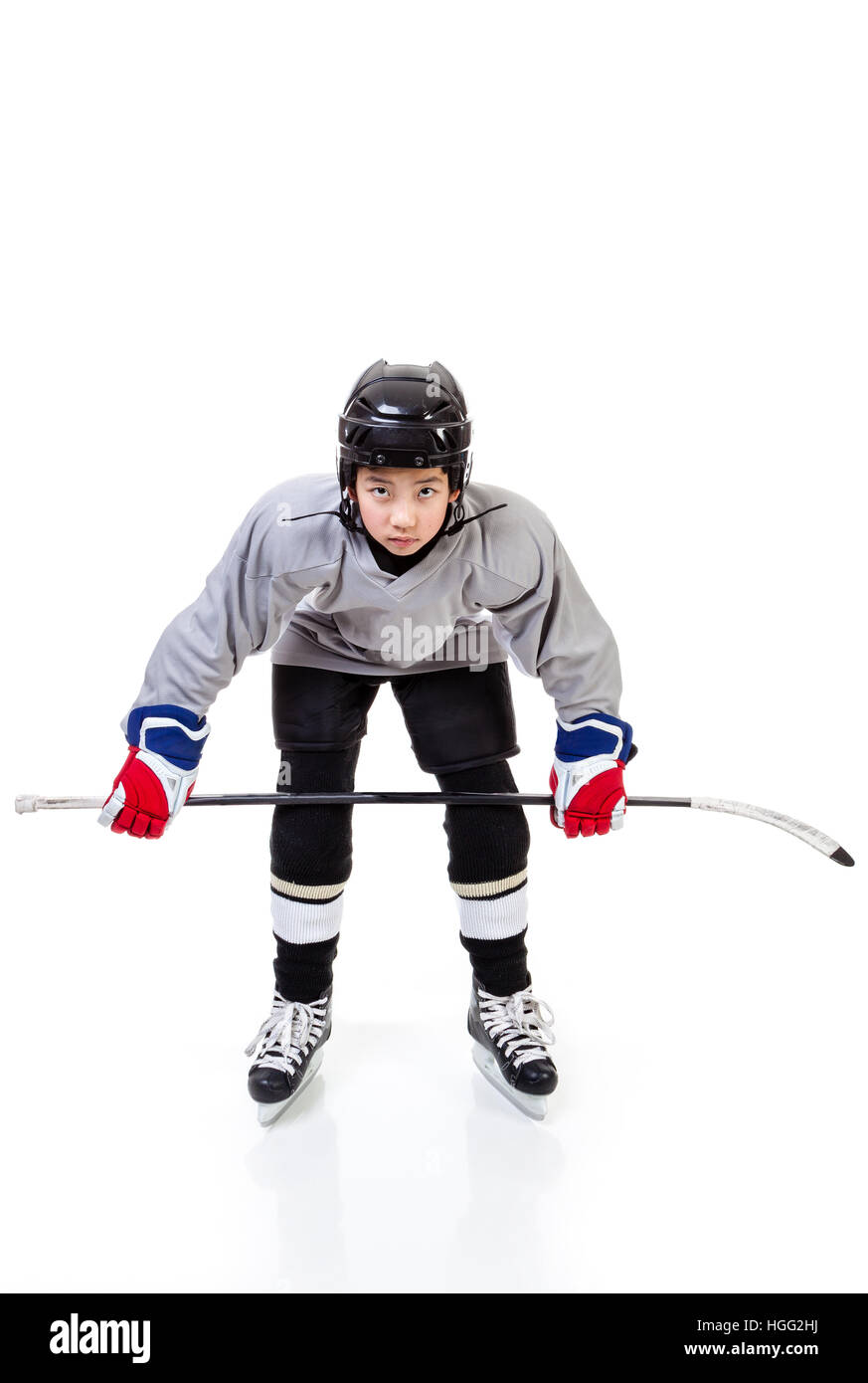 Junior ice hockey player with full equipment and uniform isolated on white background. In faceoff stance. - Stock Image