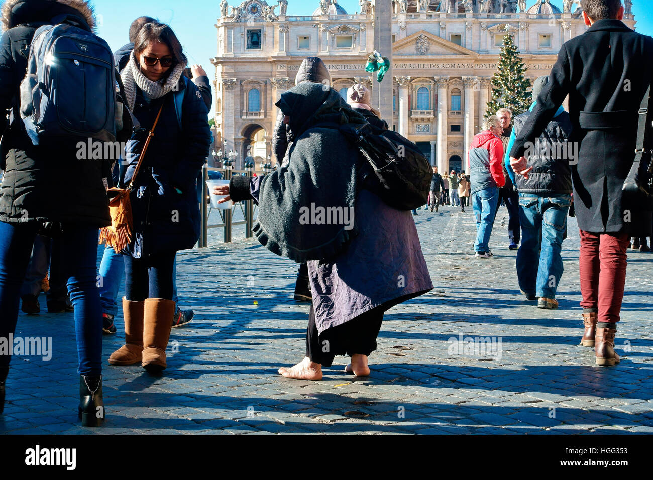 Unidentified  beggar begging among a crowd of people passing through in St. Peter's square. Vatican city, Rome, - Stock Image