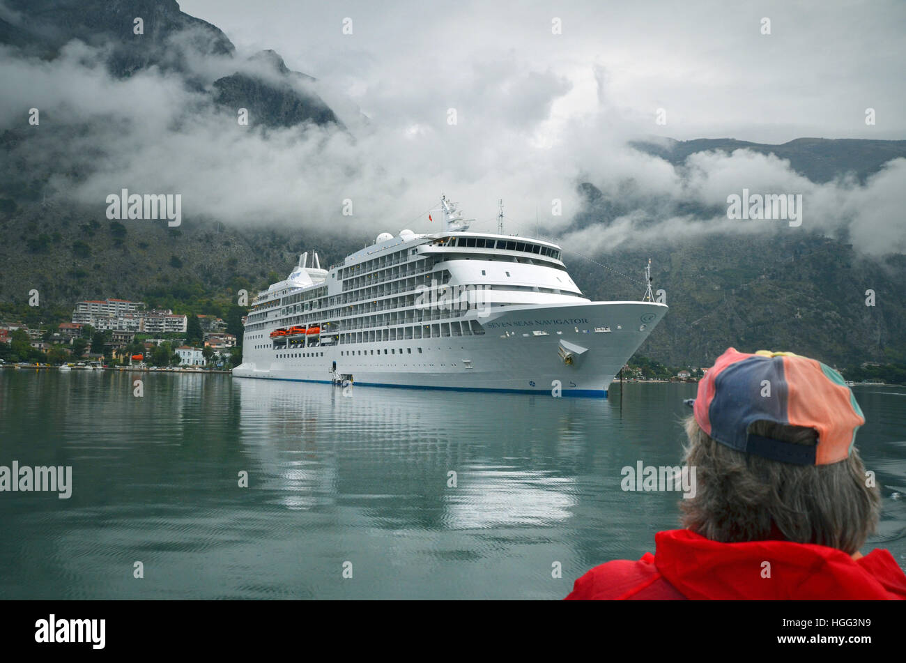 A cruise ship anchors at the Bay of Kotor in misty weather as a sightseer looks on. - Stock Image