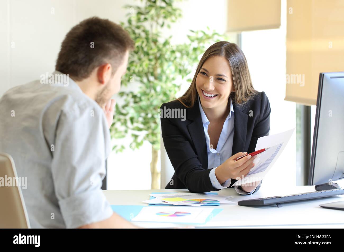 Boss showing a good job congratulating an employee at office - Stock Image