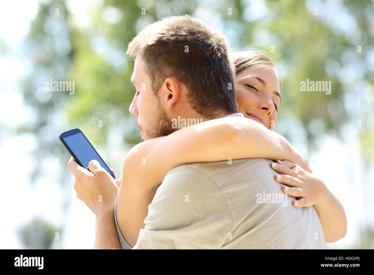 Cheater texting with his other lover on phone and hugging his innocent girlfriend - Stock Image