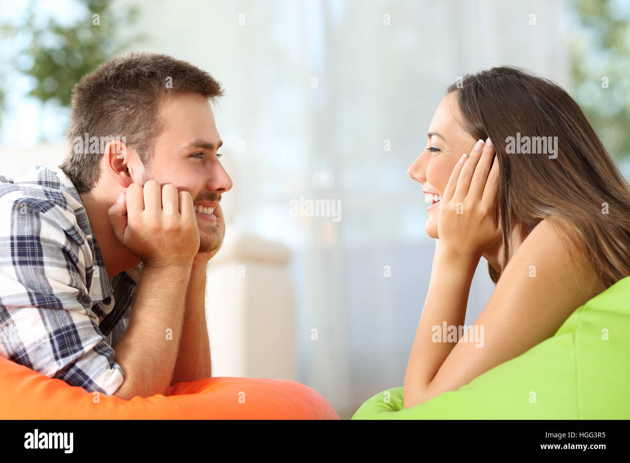 Side view of two friends falling in love looking each other lying on poufs in the living room at home - Stock Image