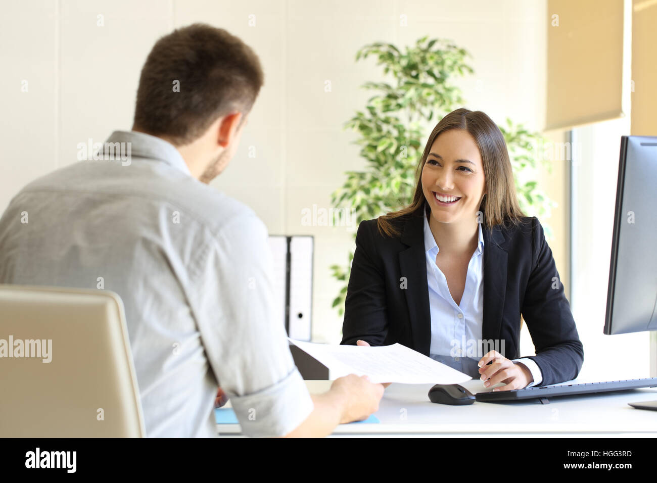 Guy giving a curriculum vitae to his interviewer in a job interview - Stock Image