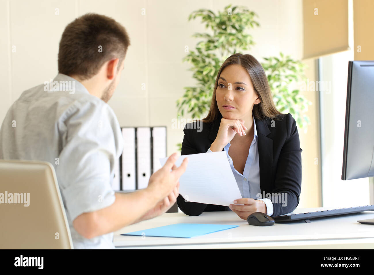 Man searching employment in a bad job interview with the interviewer looking mistrustful - Stock Image