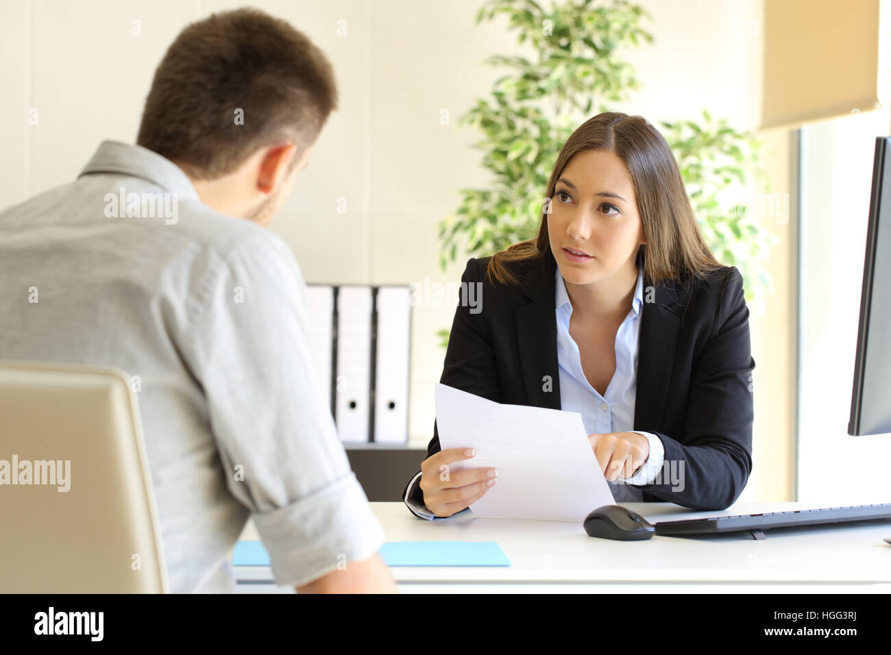 Guy and businesswoman talking in a job interview in an office - Stock Image