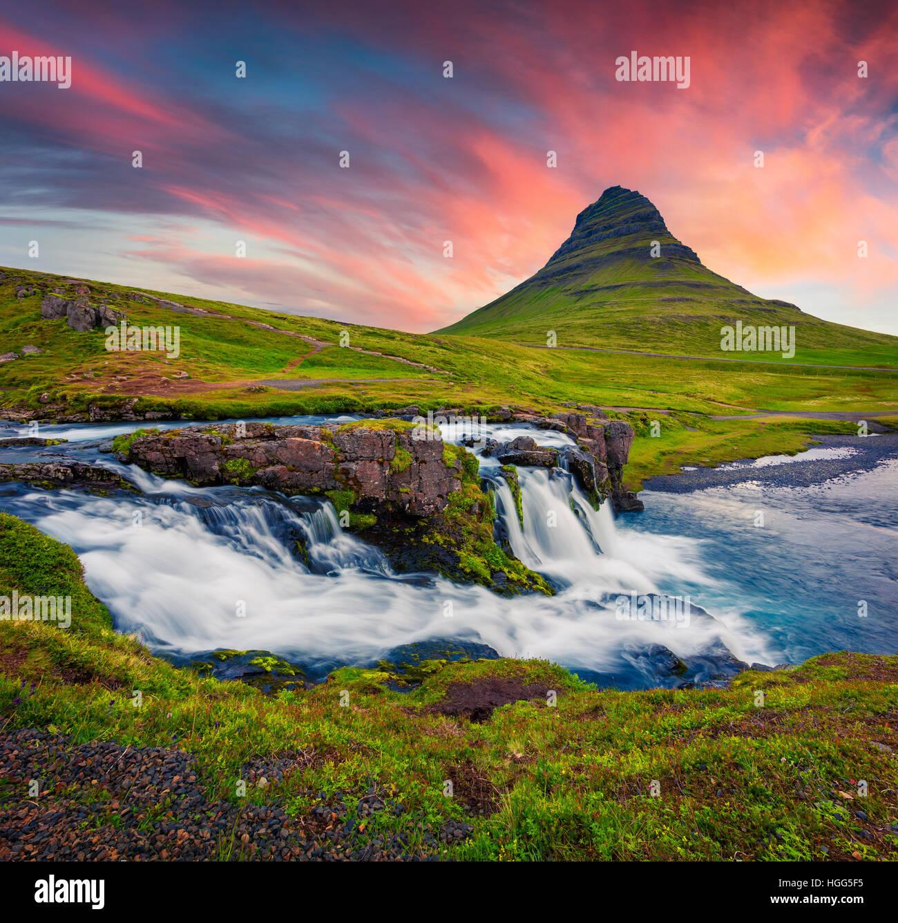 Summer sunset on famous Kirkjufellsfoss Waterfall and Kirkjufell mountain. Dramatic evening scene on Snaefellsnes - Stock Image