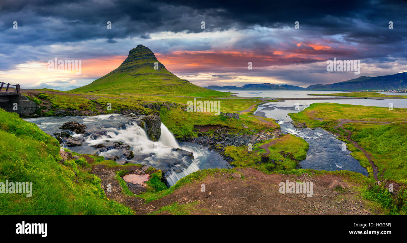 Summer sunset on famous Kirkjufellsfoss Waterfall and Kirkjufell mountain. Dramatic evening panorama of Snaefellsnes - Stock Image