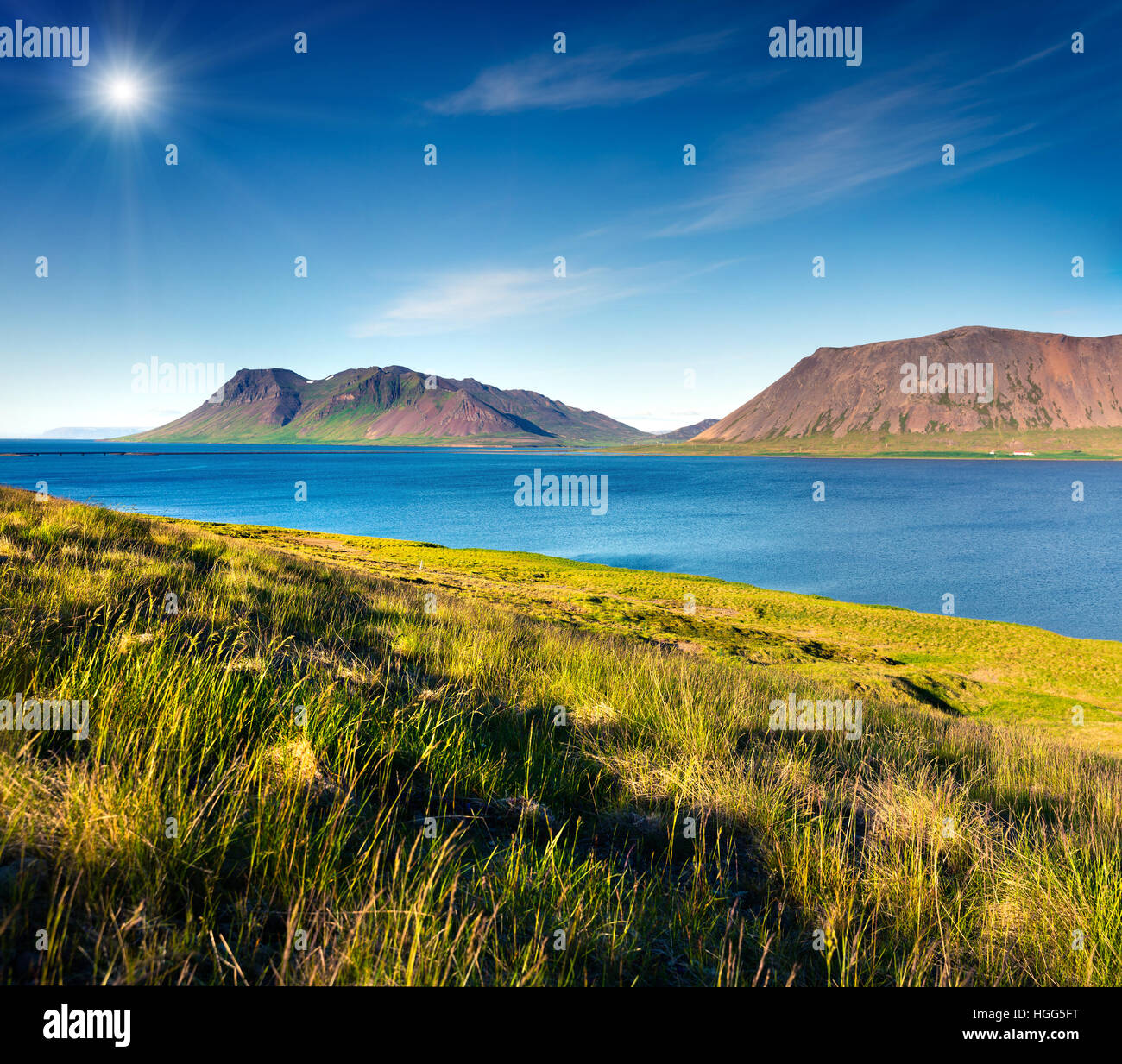 Typical Icelandic landscape with volcanic mountains and pure water river. Sunny summer morning in the west coast - Stock Image