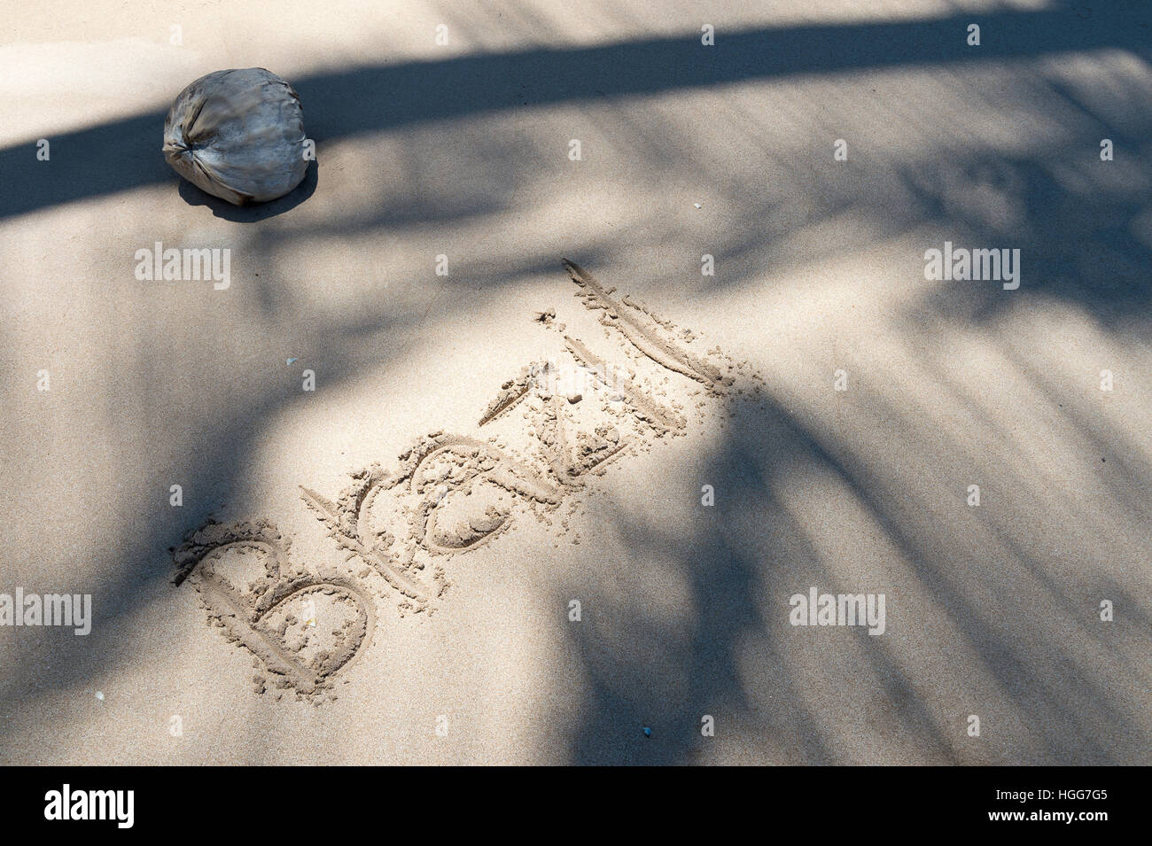 Brazil message handwritten in the sand with palm frond shadows on an empty beach in Bahia - Stock Image