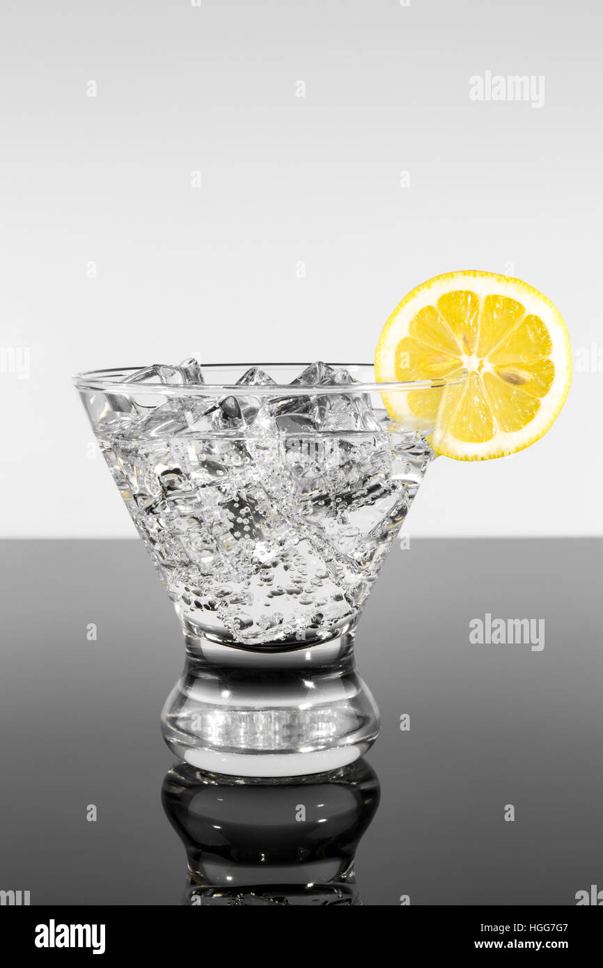 Sparkling beverage in a martini glass with a lemon slice - Stock Image