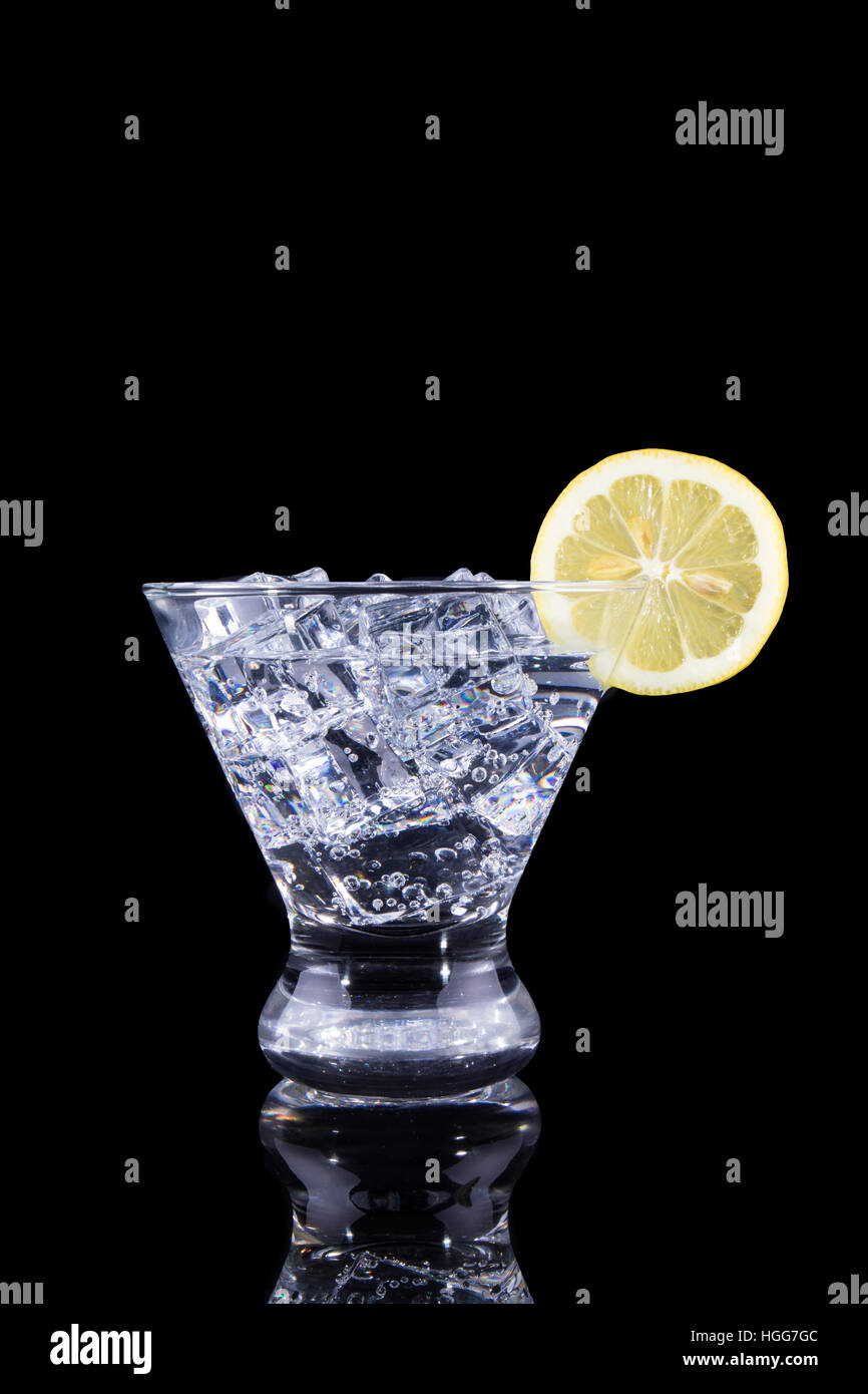 Sparkling beverage in a martini glass with a lemon slice on a black background - Stock Image