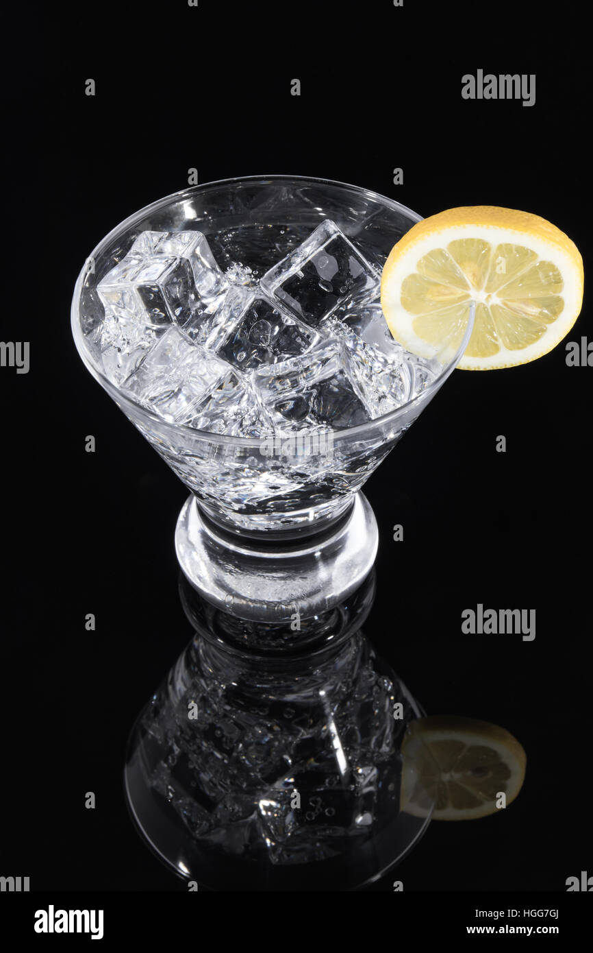 Sparkling beverage in a martini glass with a lemon slice on a black background Stock Photo