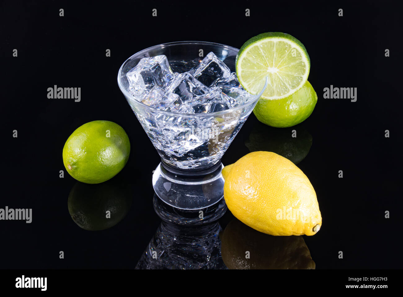Sparkling beverage in a martini glass with lemons and limes on a black background - Stock Image