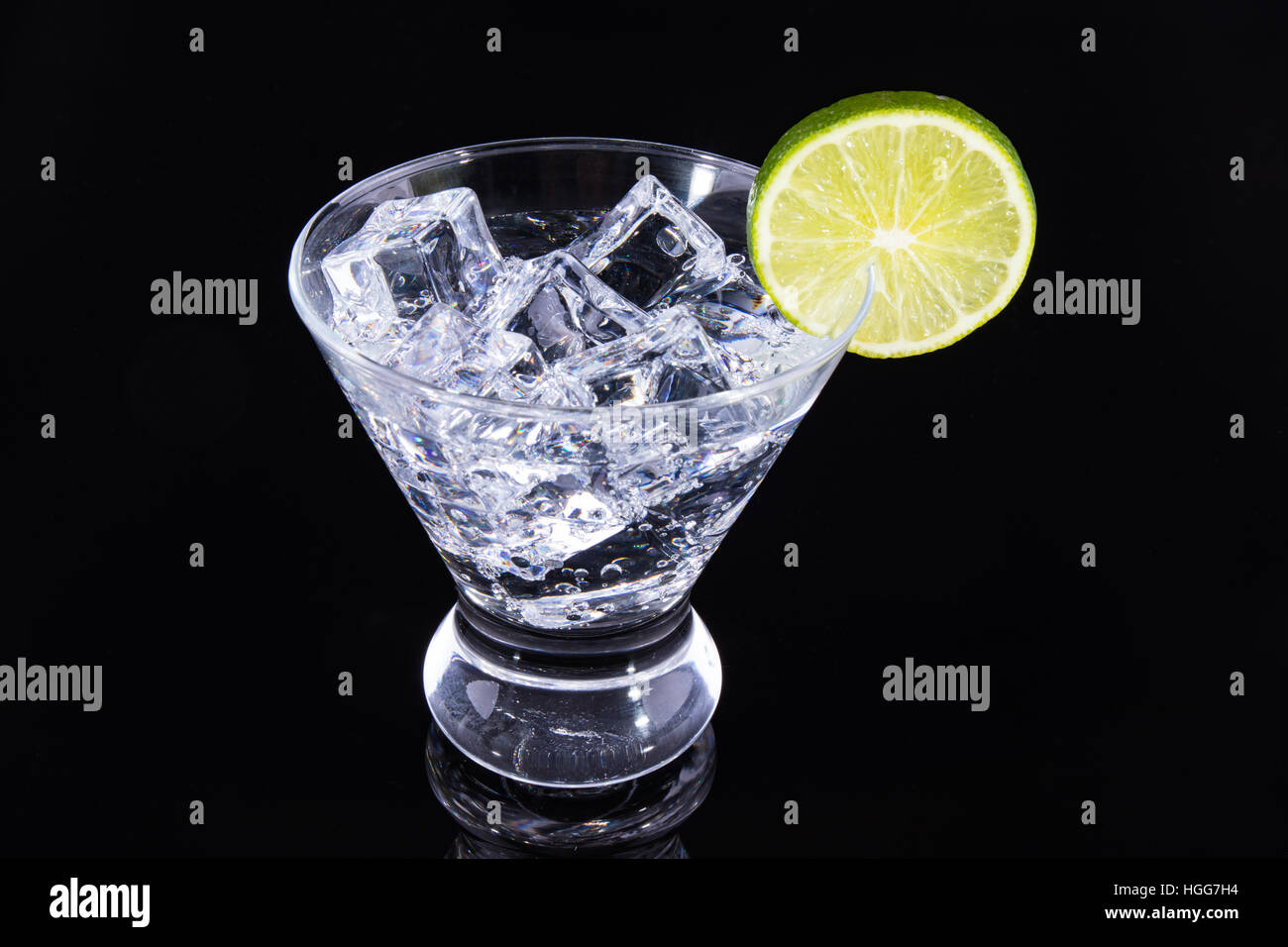 Sparkling beverage in a martini glass with a lime slice on a black background Stock Photo