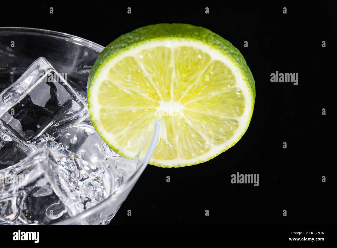 Sparkling beverage in a martini glass with a lime slice on a black background - Stock Image