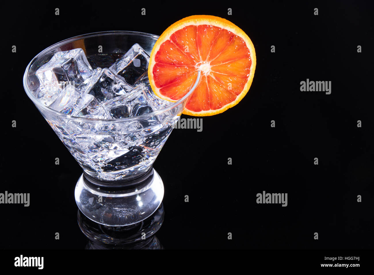 Sparkling beverage in a martini glass with a blood orange slice on a black background - Stock Image